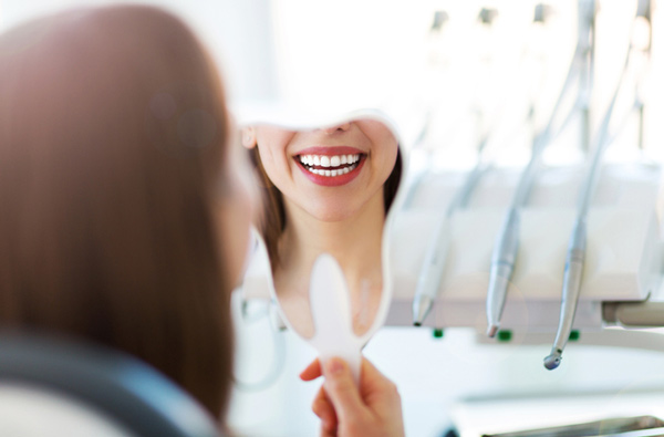 Woman looking at her smile in a mirror